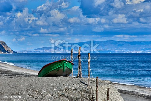 Typical colored wooden fishing boat in front of Messina strait in the province of Messina on a sunny day in early spring