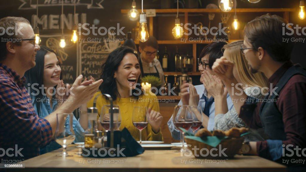 En el Bar / restaurante bella mujer hispana comparte buenas noticias con sus amigos queridos que felicitarla efusivamente y aplaudieran. Se sientan en el establecimiento con estilo Hipster. - Foto de stock de 20 a 29 años libre de derechos
