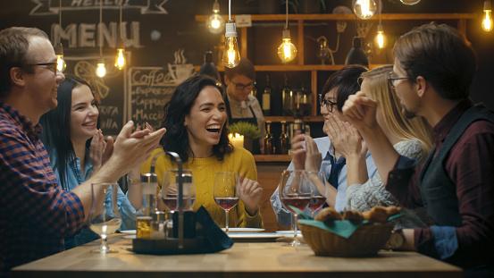 En El Bar Restaurante Bella Mujer Hispana Comparte Buenas Noticias Con Sus Amigos Queridos Que Felicitarla Efusivamente Y Aplaudieran Se Sientan En El Establecimiento Con Estilo Hipster Foto de stock y más banco de imágenes de 20 a 29 años