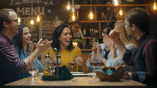 No Bar / Restaurante belo mulher hispânica compartilha boas notícias com seus amigos queridos que felicito vivamente e aplaudam. Sentam-se no estabelecimento elegante Hipster. - foto de acervo