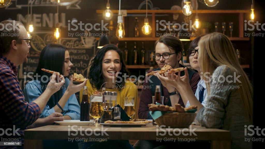 En el Bar / restaurante grupo de diversos jóvenes comer rebanadas de Pizza pastel. Hablar, contar chistes y divertirse en este elegante establecimiento. - foto de stock