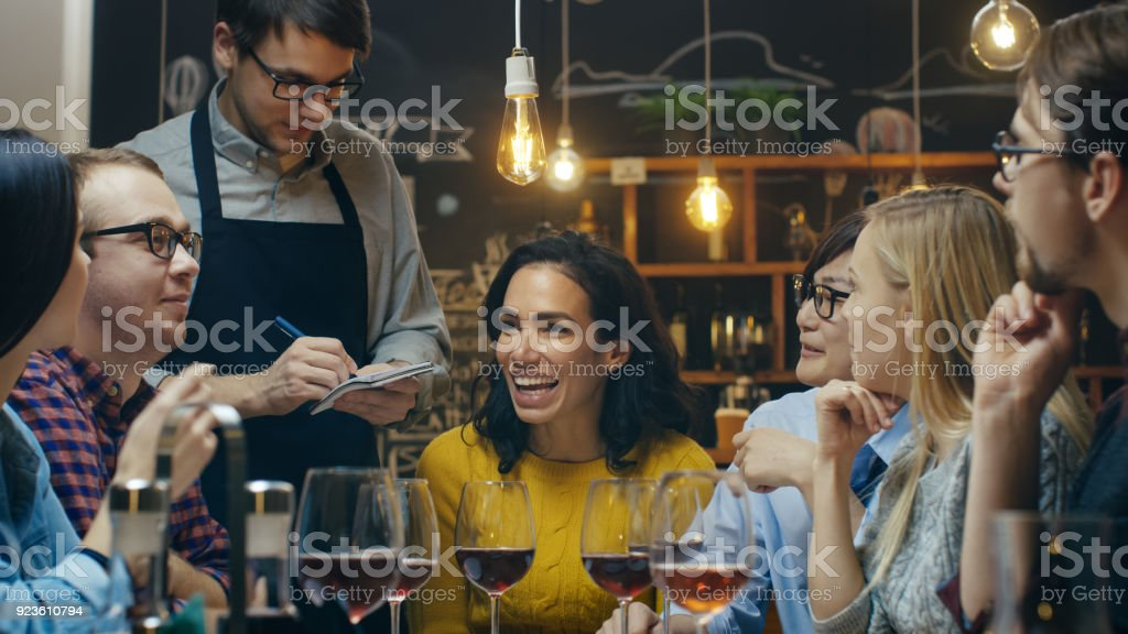 In the Bar/ Restaurant Waiter Takes Order From a Diverse Group of Friends. Beautiful People Drink Wine and Have Good Time in this Stylish Place. stock photo