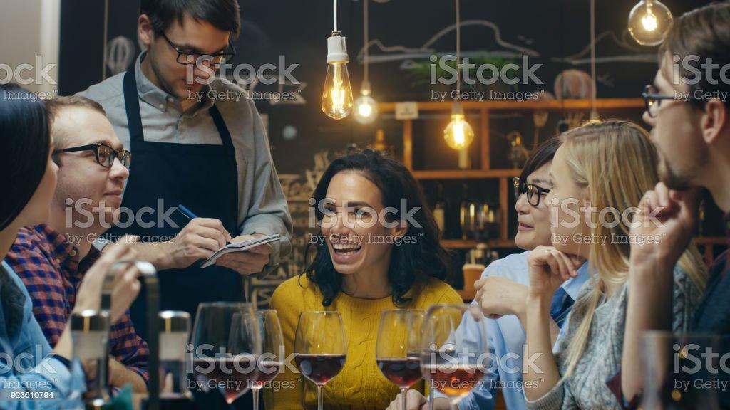 En el Bar / restaurante camarero lleva orden de un diverso grupo de amigos. Hermosa gente beber vino y tener buen tiempo en este lugar con estilo. - foto de stock