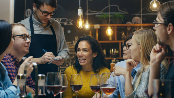 In the Bar/ Restaurant Waiter Takes Order From a Diverse Group of Friends. Beautiful People Drink Wine and Have Good Time in this Stylish Place. - foto stock