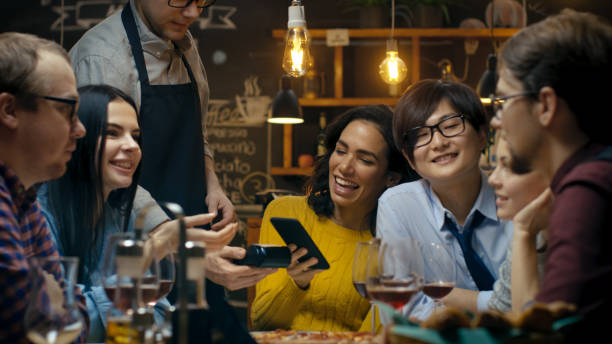 in the bar waiter holds credit card payment machine and beautiful woman pays for her order with contactless mobile phone payments system. she has good time with her friends. - paying with card contactless imagens e fotografias de stock