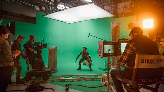 In the Big Film Studio Professional Crew Shooting Blockbuster Movie. Director Commands Cameraman to Start shooting Green Screen CGI Scene with Actor Wearing Motion Capture Suit and Head Rig