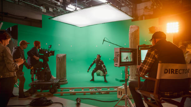 In the Big Film Studio Professional Crew Shooting Blockbuster Movie. Director Commands Cameraman to Start shooting Green Screen CGI Scene with Actor Wearing Motion Capture Suit and Head Rig stock photo