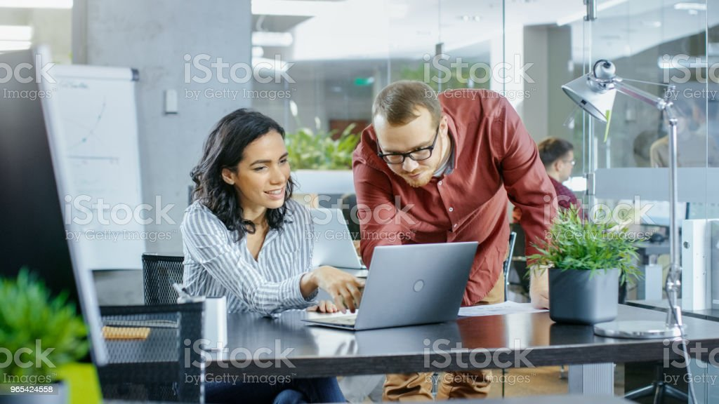 In the Busy Corporate Office Male and Female Have Work Related Discussion, Using Personal Computer. In the Background Creative Young People Working. zbiór zdjęć royalty-free