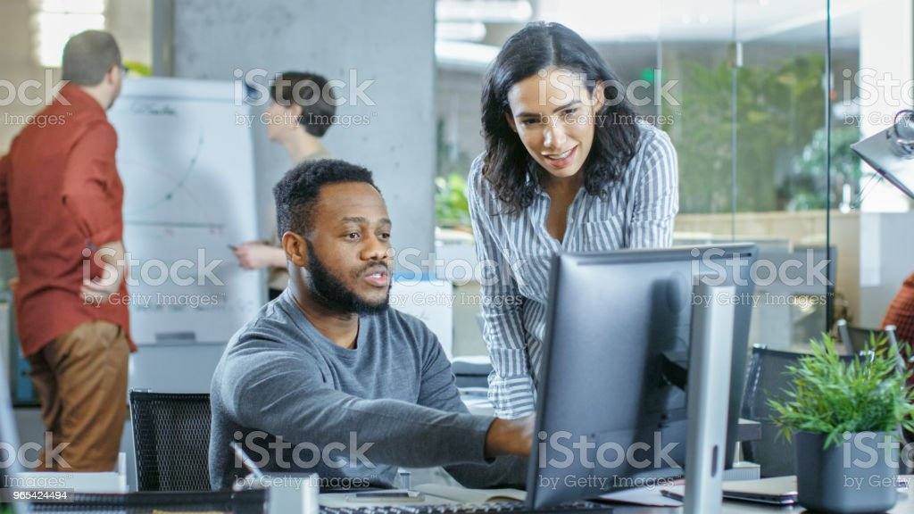In the Busy Corporate Office Male and Female Together Solve Work Related Problems, Using Personal Computer. In the Background Creative Young People Working. royalty-free stock photo