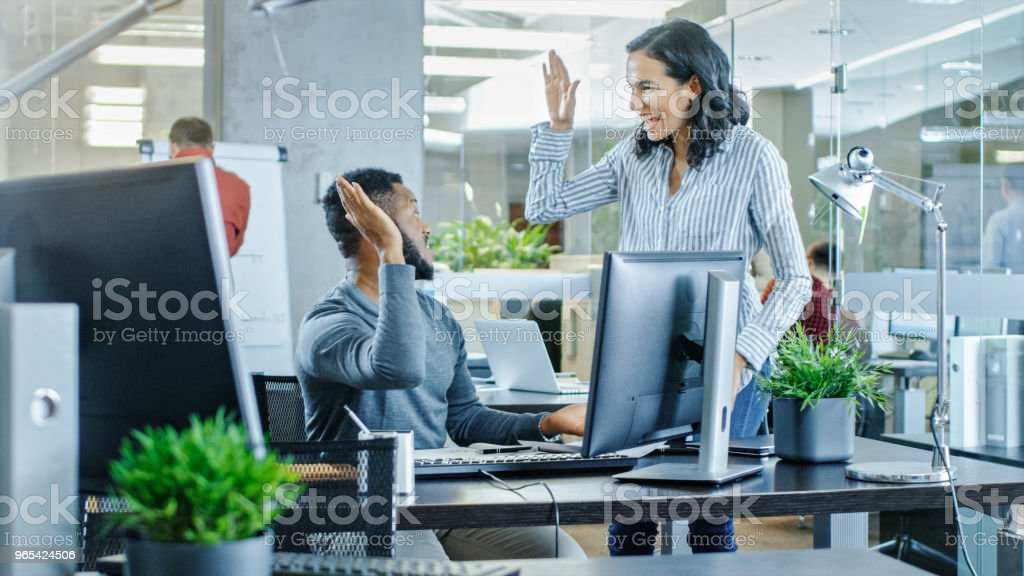 In the Busy Corporate Office Male and Female Together Solve Work Related Problems, Using Personal Computer. They Do High-Five. In the Background Creative Young People Working. royalty-free stock photo