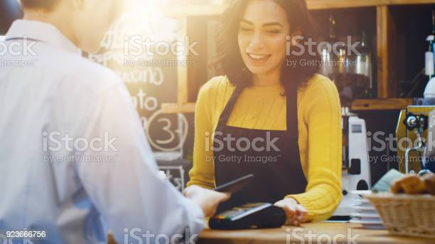 In the cafe beautiful hispanic woman makes takeaway coffee for a who picture id923666756?b=1&k=6&m=923666756&s=612x612&h=kywn4x5ryf1azyoym0elnu lynnqrh8d3 jfqr1xo14=