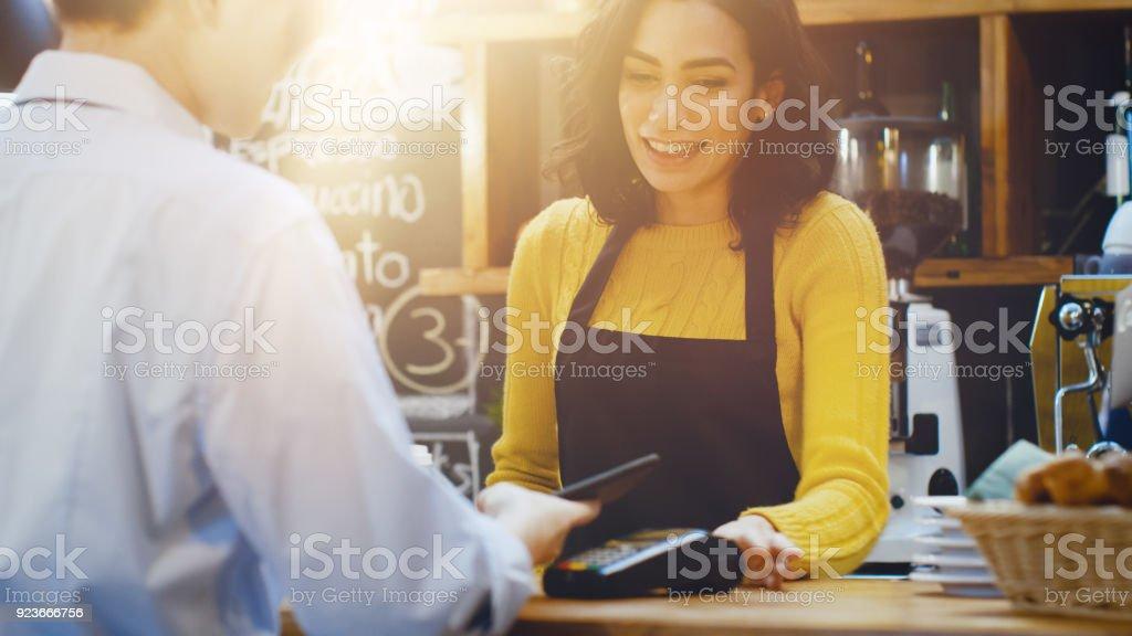 I Cafe gör vackra spansktalande kvinna Takeaway-kaffe för en kund som betalar av kontaktlösa mobiltelefon till kreditkortssystem. bildbanksfoto