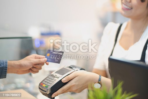 In the Cafe, Customer using credit card Makes a Pays to Woman by cashless technology System. Contact less payment concept.