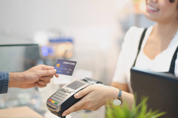 In the Cafe, Customer using credit card Makes a Pays to Woman by cashless technology System. Contact less payment concept. In the Cafe, Customer using credit card Makes a Pays to Woman by cashless technology System. Contact less payment concept. market vendor stock pictures, royalty-free photos & images