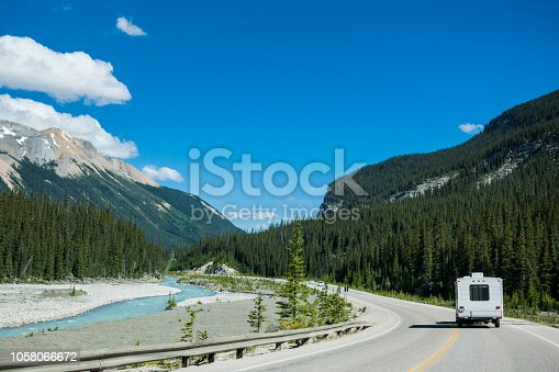 Recreational vehicle driving through the beautiful wilderness landscape of the Canadian Rockies in Banff National Park, Alberta, Canada.