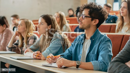 istock In the Classroom Multi Ethnic Students Listening to a Lecturer and Writing in Notebooks. Smart Young People Study at the College. 962475722