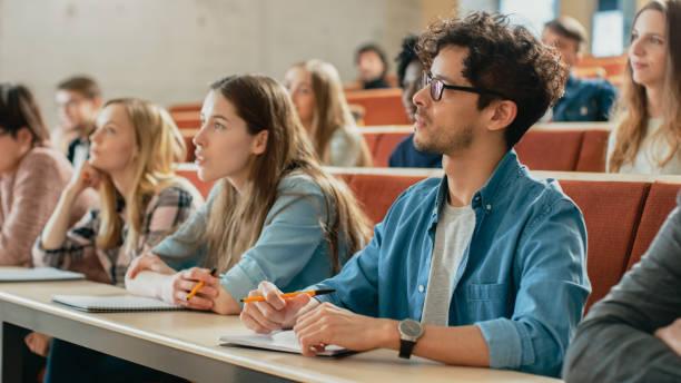 en el aula multi étnica estudiantes escuchando a un profesor y escribir en los cuadernos. jóvenes inteligente estudio en la universidad. - estudiante fotografías e imágenes de stock