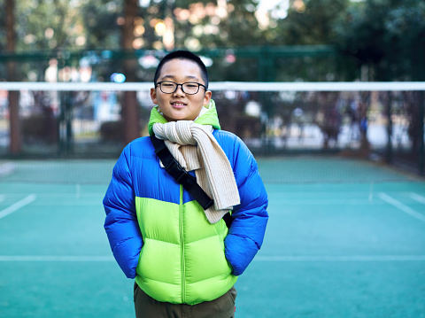 In the cold winter, a happy teenager wearing a blue down jacket looks at the camera and smiles in an outdoor badminton court。Chinese teenagers wear Beige scarves and smile at the camera