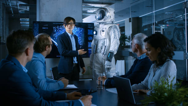 In the Conference Room Chief Engineer Presents Next Generation Space Suit to a Board of Directors. Completely Original Design with Integrated AI and Neural Network Systems. New Level of Space Travel. stock photo
