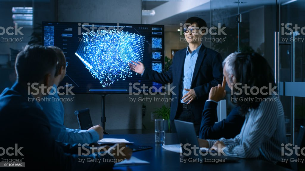 In the Conference Room Chief Engineer Presents to a Board of Scientists New Revolutionary Approach for Developing Artificial Intelligence and Neural Networks. Wall TV Shows Their Achievements. royalty-free stock photo