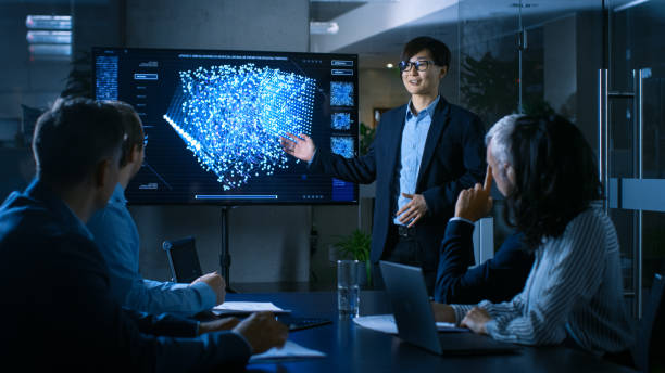 In the Conference Room Chief Engineer Presents to a Board of Scientists New Revolutionary Approach for Developing Artificial Intelligence and Neural Networks. Wall TV Shows Their Achievements. stock photo