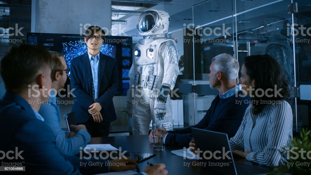 In the Conference Room of the Center of Technology Chief Engineer Presents Next Generation Space Suit to a Board of Directors. Completely Original Design with Integrated AI and Neural Network Systems. stock photo