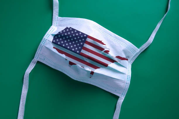 USA in the Coronavirus pandemic, white face mask with USA map and flag stock photo