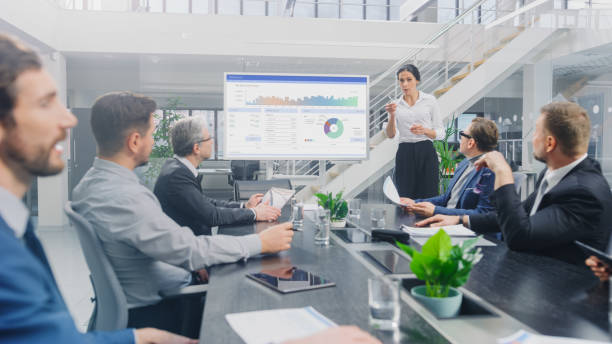In the Corporate Meeting Room: Female Analyst Uses Digital Interactive Whiteboard for Presentation to a Board of Executives, Lawyers, Investors. Screen Shows Company Growth Data with Graphs stock photo