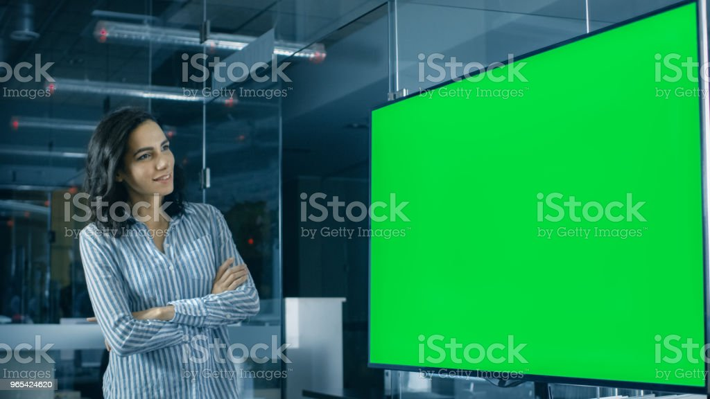 In the Corporate Office Beautiful Hispanic Woman Analyzes Green Screen Chroma Key Template Shown on a Wall TV. zbiór zdjęć royalty-free