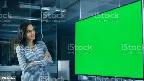 Foto de A Sede Da Linda Mulher Hispânica Analisa Tela Verde Chroma Chave Modelo Mostrado Em Uma Tv De Parede e mais fotos de stock de Adulto