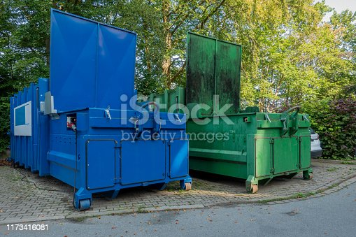 in the courtyard of a hospital there are two garbage compactors next to each other, one for garbage, the other for paper and cardboard