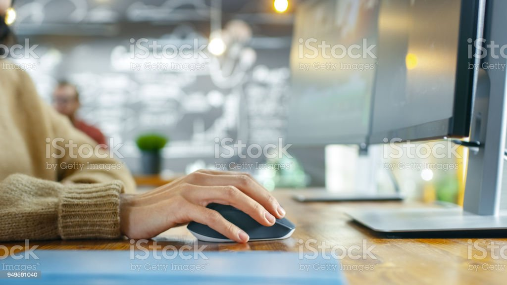 In the Creative Agency Close-up of the Woman's Hand Using Mouse and Typing on Her Personal Computer. In the Background Her Colleague Working on the Project. stock photo