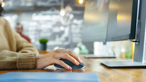 In der Kreativagentur Nahaufnahme von die Frau Hand mit Maus und tippen auf ihrem PC. Im Hintergrund ihrer Kollegin, die an dem Projekt arbeiten. – Foto