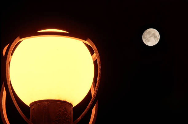 In the dark, a spherical street lamp made of frosted glass shines. In the background is a round moon with a distinguishable surface structure. Background. In the dark, a spherical street lamp made of frosted glass shines. In the background is a round moon with a distinguishable surface structure. Background. irradiation stock pictures, royalty-free photos & images