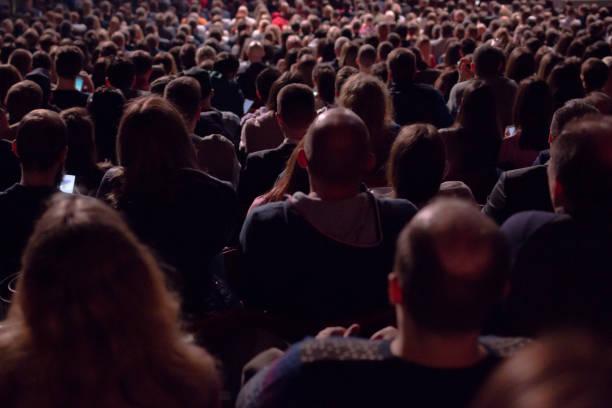 暗いホールには、映画館や舞台で上映される何百人もの人々の群衆の後ろから景色が見えます。 - オペラ ストックフォトと画像