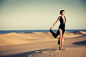 Young woman in night gown and high heels standing on top of a dune in the desert. Saturated warm tones.