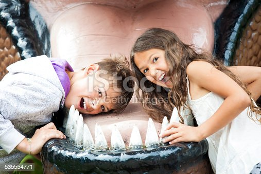 Two happy children are having fun pretending to be in the dinosaur jaw