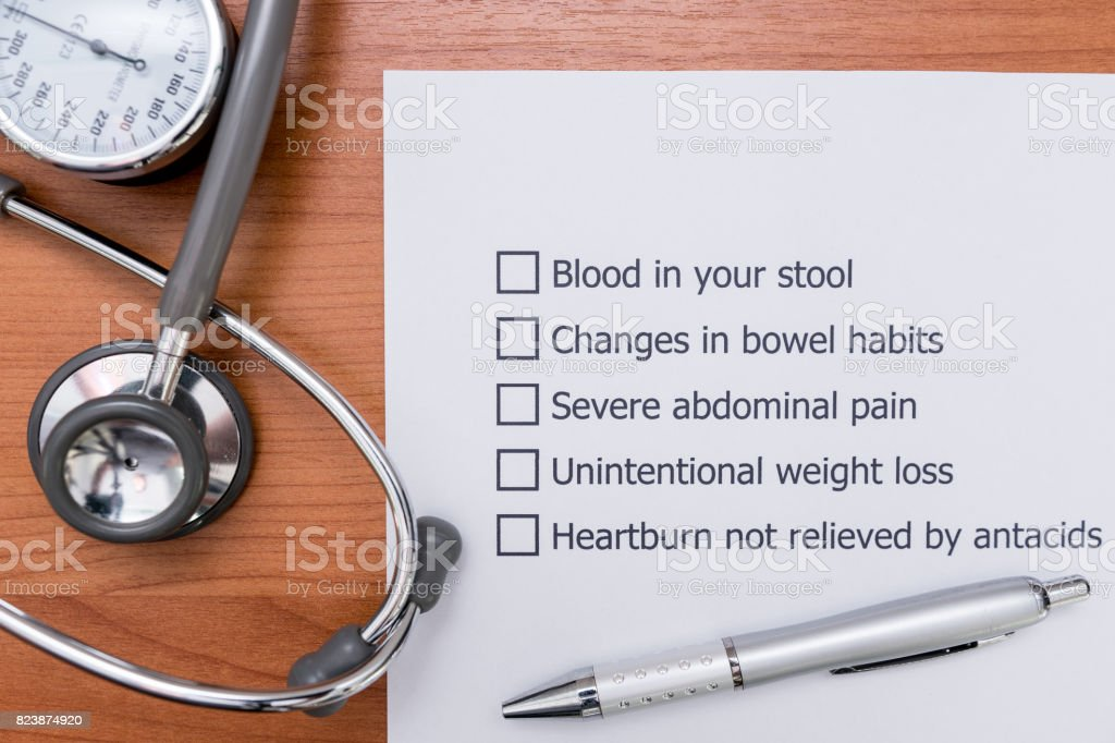 In the doctor's Office There is a form that the doctor made to diagnose the disease that indicate Colon Cancer in a patient. Diagnosis form placed on the doctor's desk. stock photo