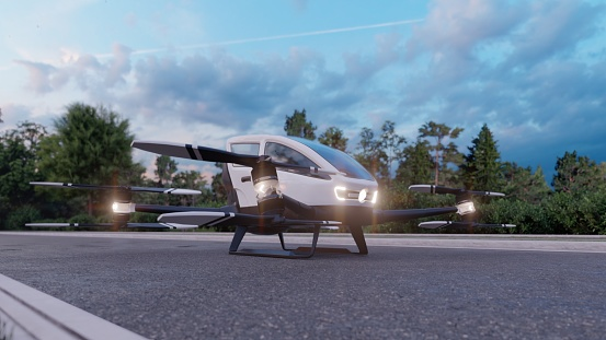 In the early morning, a high-tech air taxi departs for its destination. View of an unmanned aerial passenger vehicle standing on the road.