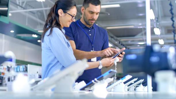 在電子商店給專業顧問向一名年輕女子,她認為買台新的平板電腦,需要專家的意見。商店是現代,明亮,所有新的設備。 - 商店 個照片及圖片檔