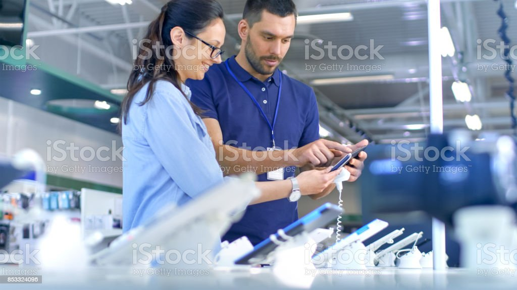 In the Electronics Store Consultant Gives Professional Advice to a Young Woman, She Considers Buying New Tablet Computer and Needs Expert Opinion. Store is Modern, Bright and Has all the New Devices. stock photo