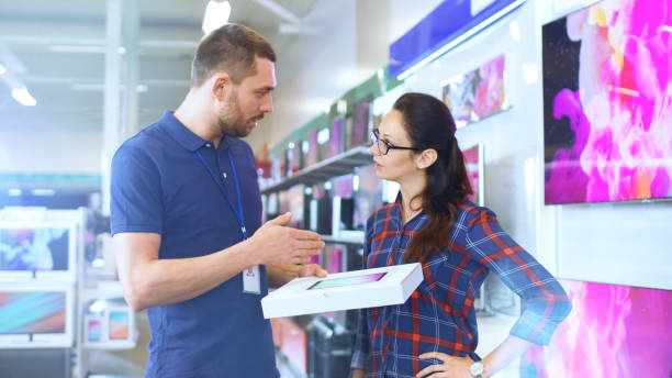In the Electronics Store Professional Consultant Provides Expert Advice on Tablet Computer Specifications For Beautiful Young Woman. Store is Bright, Modern and Has all the Latest Devices. stock photo
