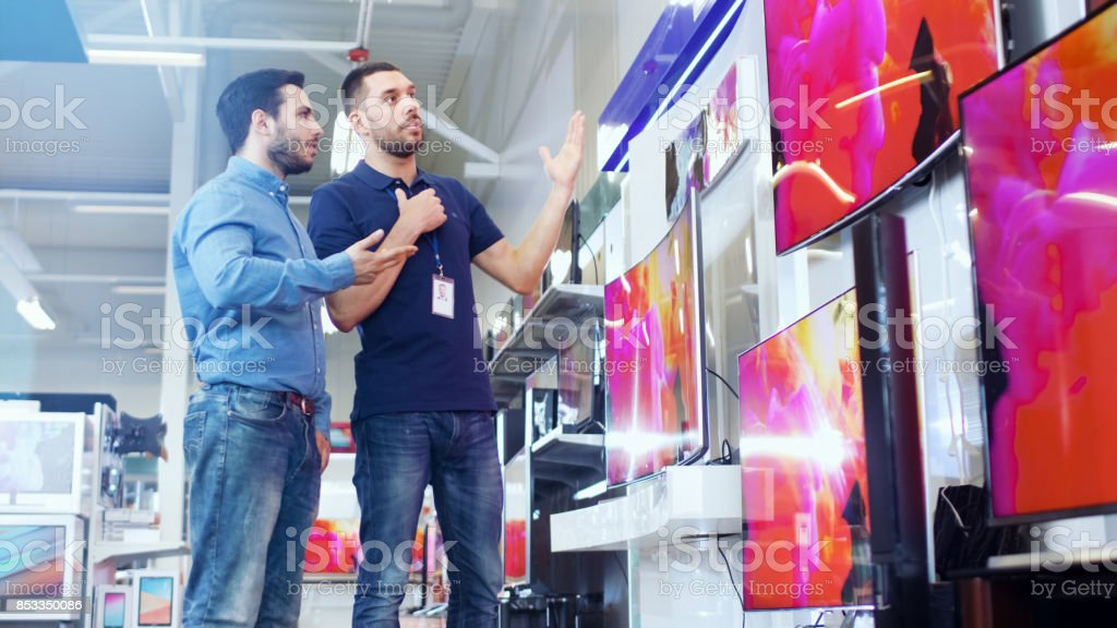 In the Electronics Store Professional Consultant Shows Latest 4K UHD TV's to a Young Man, They Talk about Specifications and What Model is Best for Young Man's Home. Store is Bright, Modern and Has all the Latest Models. stock photo