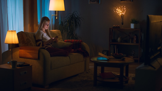 In the Evening Beautiful Young Woman Relaxes on a Couch in Her Cozy Living Room. She Uses Her Smartphone.