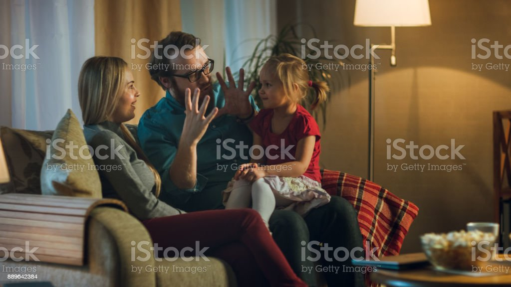 In the Evening Family Spends Time Together Sitting on a Couch in a Living Room. Little Girl Sits on Her Father's Laps and Parents Tickle Her. stock photo