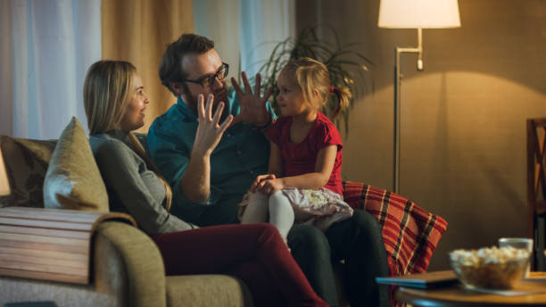 in die abend-familie verbringt zeit zusammen sitzen auf einer couch im wohnzimmer. kleines mädchen sitzt auf ihres vaters schoß und eltern kitzeln. - kids tv zimmer stock-fotos und bilder