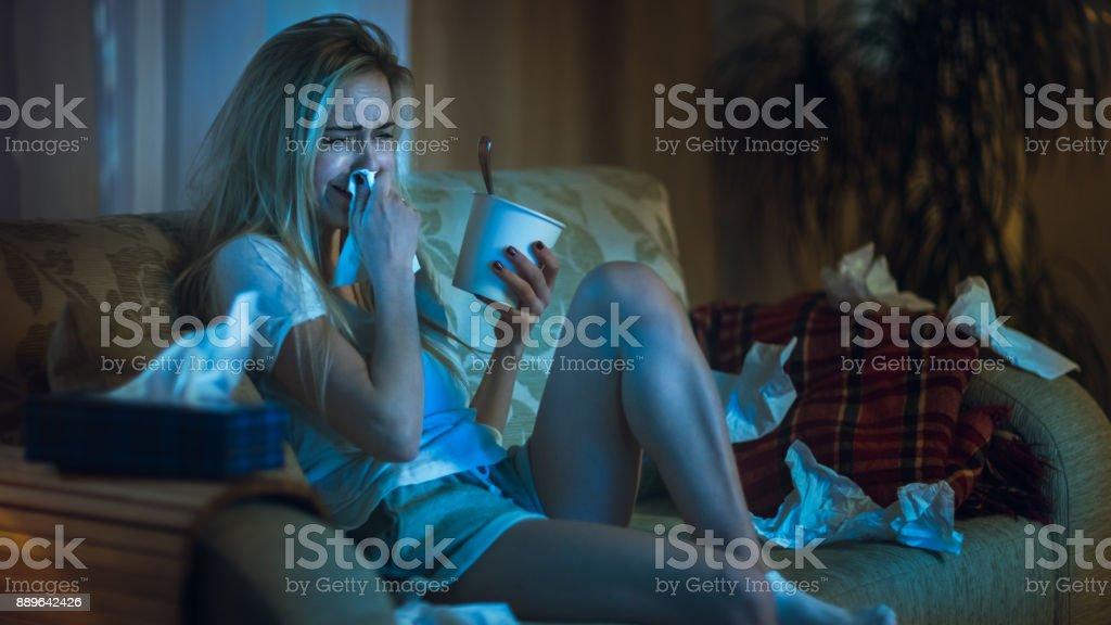 In den Abend mit gebrochenem Herzen Mädchen sitzen auf einem Sofa, weinend, mit Gewebe, Eis essen und Drama im Fernsehen beobachten. Ihr Zimmer ist im Chaos. – Foto