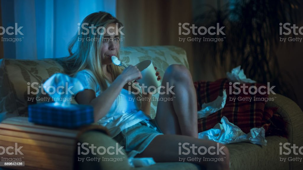 In the Evening Heartbroken Girl Sitting on a Sofa, Crying, Using Tissues, Eating Ice Cream and Watching Drama on TV. Her Room is in Mess. stock photo