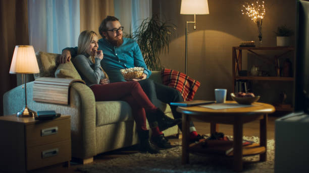In the Evening Man and Woman are Sitting on the Sofa Watching TV and Eating Popcorn. Living Room is Cozy. stock photo