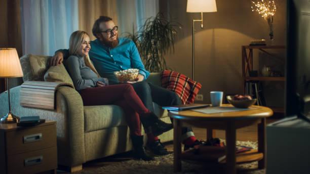 en el hombre de la noche y la mujer están sentados en el sofá viendo tv y comiendo palomitas. sala de estar es acogedor. - sequence animation fotografías e imágenes de stock